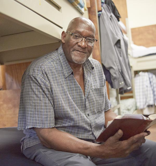 Homeless man reading at rescue mission